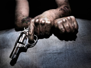 """A man with tattoos including """"love"""" and """"hate"""" holding a pistol.A man with tattoos including """"love"""" and """"hate"""" holding a pistol."""